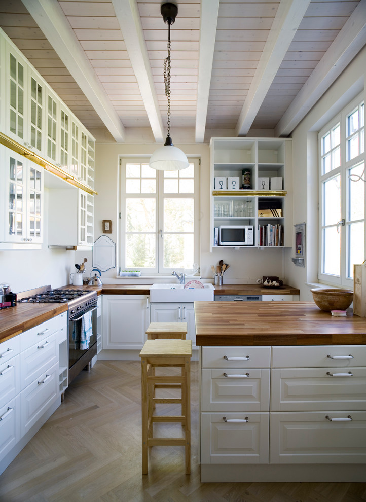 Mid-sized farmhouse l-shaped light wood floor kitchen photo in Berlin with a drop-in sink, beaded inset cabinets, white cabinets, wood countertops, white backsplash, stainless steel appliances and a peninsula