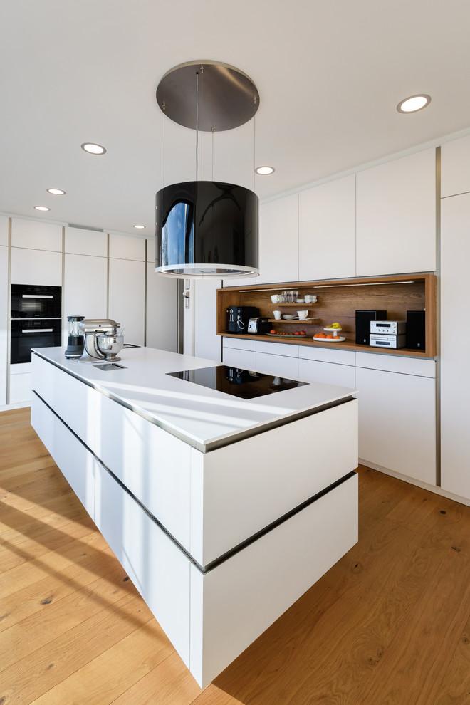 Offene, Mittelgroße Moderne Küche in L-Form mit integriertem Waschbecken, flächenbündigen Schrankfronten, weißen Schränken, Mineralwerkstoff-Arbeitsplatte, Küchenrückwand in Weiß, Rückwand aus Holz, schwarzen Elektrogeräten, gebeiztem Holzboden, Kücheninsel und braunem Boden in Stuttgart