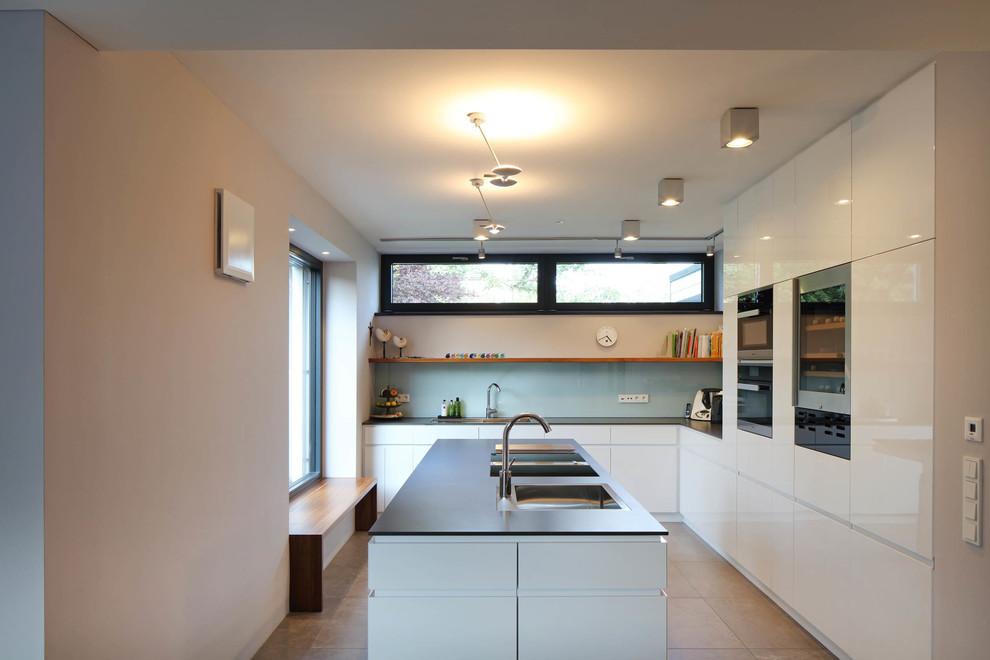 Offene, Mittelgroße Moderne Küche in L-Form mit Kücheninsel, Einbauwaschbecken, flächenbündigen Schrankfronten, weißen Schränken, Küchenrückwand in Blau, Glasrückwand, schwarzen Elektrogeräten, Zementfliesen und beigem Boden in Stuttgart