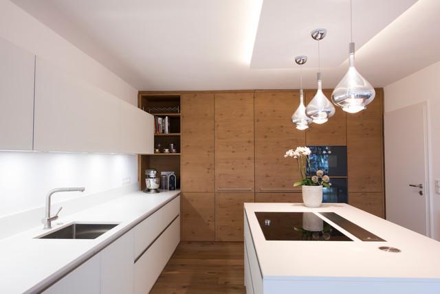 Moderne Küche in L-Form mit Unterbauwaschbecken, flächenbündigen Schrankfronten, weißen Schränken, Küchenrückwand in Weiß, schwarzen Elektrogeräten und Kücheninsel in Sonstige