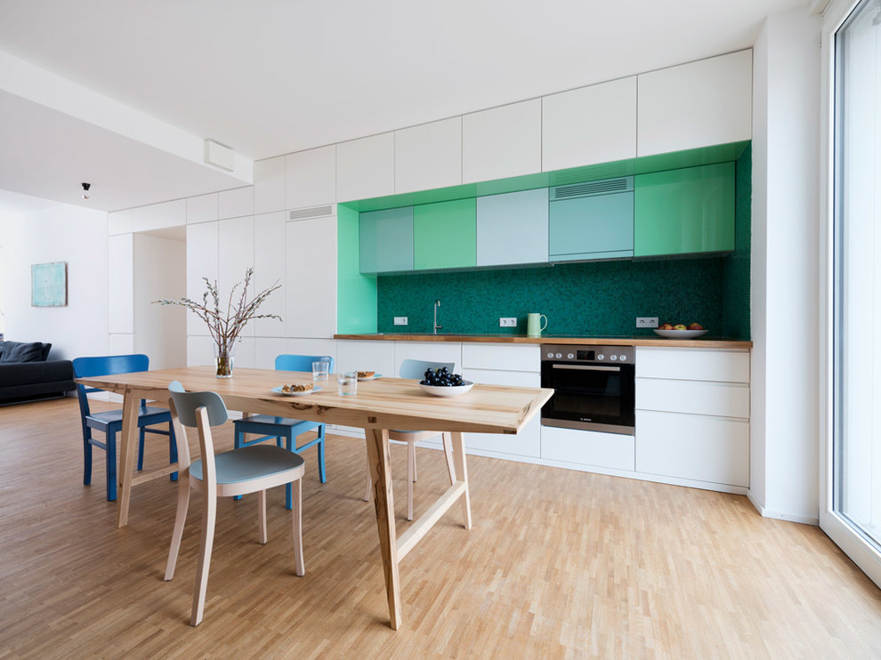 Inspiration for a large scandinavian single-wall light wood floor eat-in kitchen remodel in Munich with flat-panel cabinets, white cabinets, wood countertops, green backsplash and stainless steel appliances