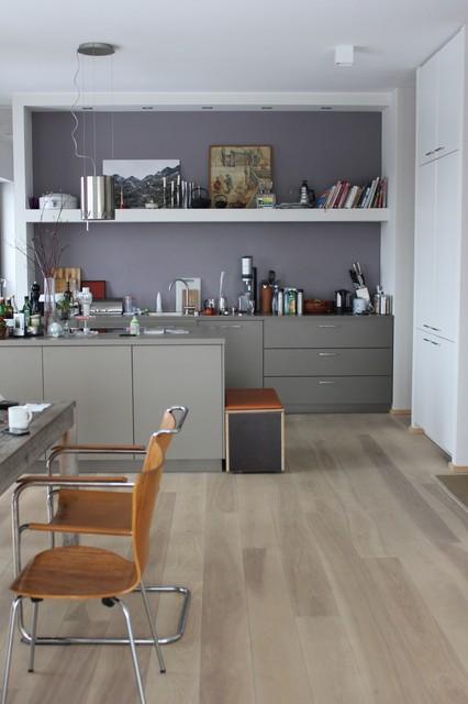 Mittelgroße Moderne Wohnküche mit flächenbündigen Schrankfronten, grauen Schränken, braunem Holzboden, Einbauwaschbecken und Kücheninsel in Berlin