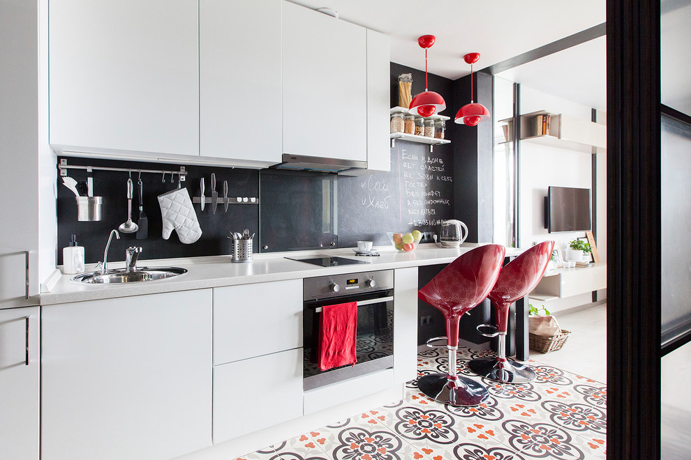 Example of a small danish single-wall porcelain tile and multicolored floor open concept kitchen design in Moscow with a drop-in sink, flat-panel cabinets, white cabinets, solid surface countertops, black backsplash, glass sheet backsplash, stainless steel appliances, gray countertops and no island