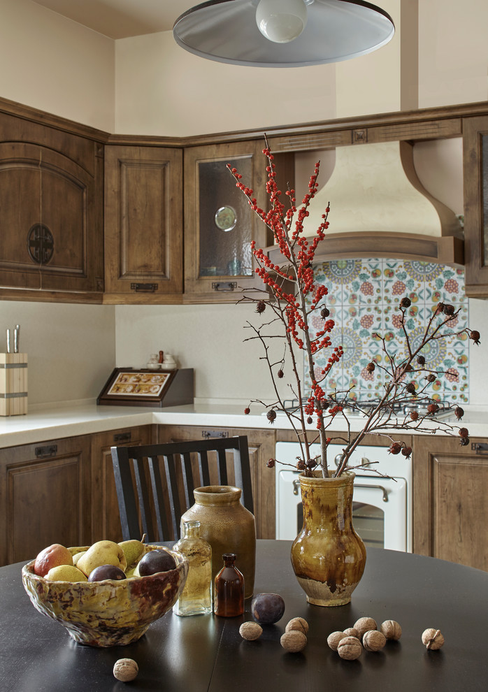 Kitchen - mid-sized country galley ceramic tile and beige floor kitchen idea in Moscow with raised-panel cabinets, medium tone wood cabinets, white backsplash, white appliances, no island, an integrated sink, solid surface countertops and stone slab backsplash