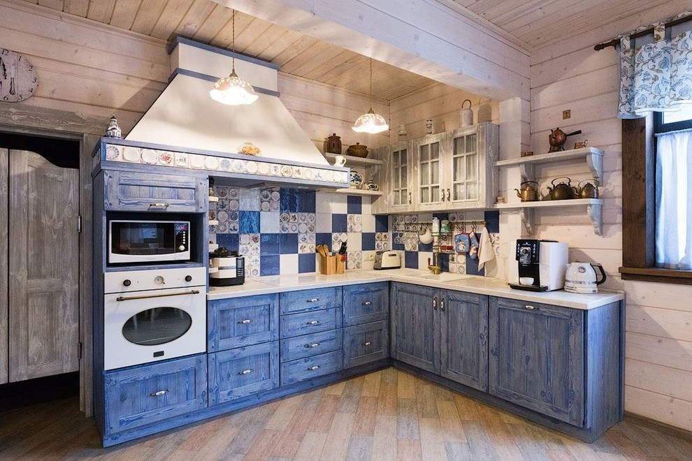Open concept kitchen - large farmhouse l-shaped porcelain tile open concept kitchen idea in Moscow with raised-panel cabinets, blue cabinets, wood countertops, ceramic backsplash, white appliances, an island, a drop-in sink and multicolored backsplash