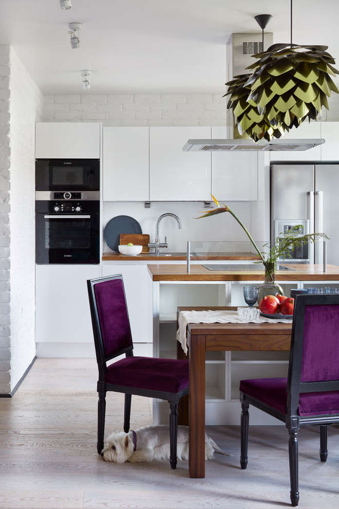 Example of a mid-sized trendy galley beige floor eat-in kitchen design in Moscow with a drop-in sink, flat-panel cabinets, white cabinets, wood countertops, white backsplash, stainless steel appliances, an island and brown countertops