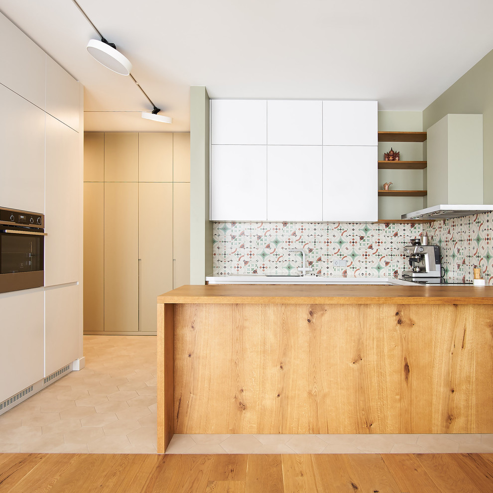 Inspiration for a contemporary u-shaped beige floor kitchen remodel in Other with flat-panel cabinets, white cabinets, wood countertops, multicolored backsplash, stainless steel appliances, a peninsula and brown countertops
