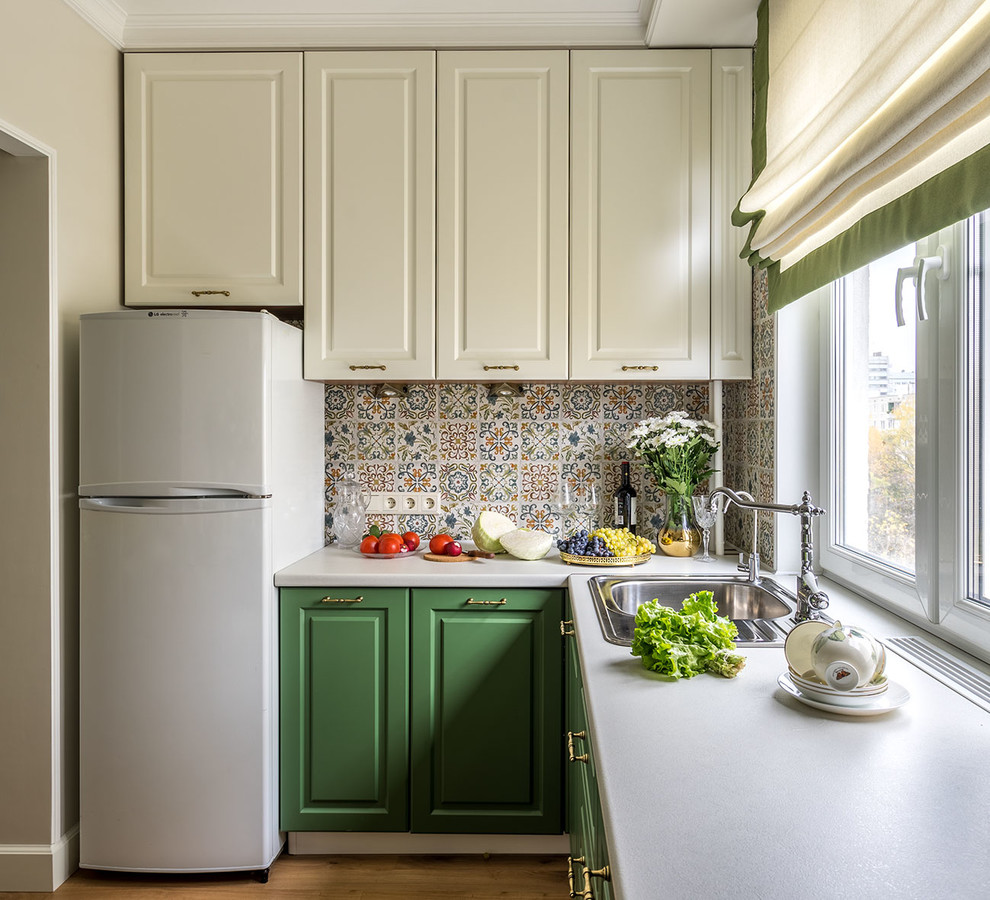 Small transitional l-shaped enclosed kitchen photo in Moscow with raised-panel cabinets, green cabinets, laminate countertops, ceramic backsplash, no island, a drop-in sink and multicolored backsplash