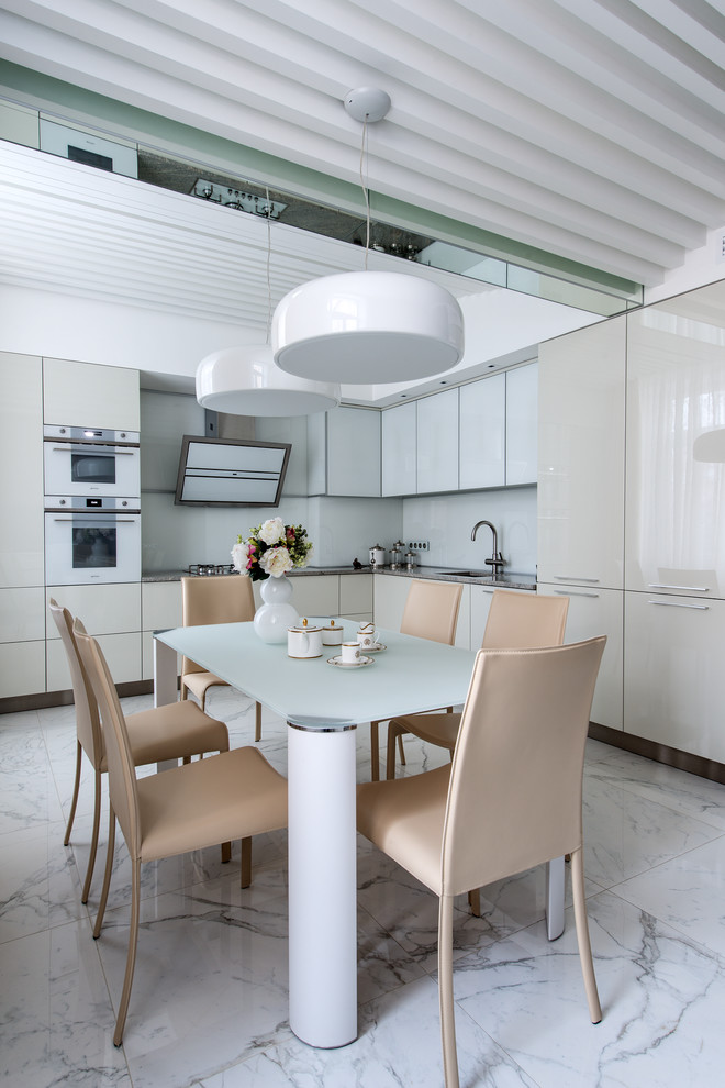 Example of a mid-sized trendy l-shaped ceramic tile and white floor eat-in kitchen design in Moscow with an undermount sink, flat-panel cabinets, gray cabinets, granite countertops, white backsplash, glass sheet backsplash, white appliances, no island and gray countertops