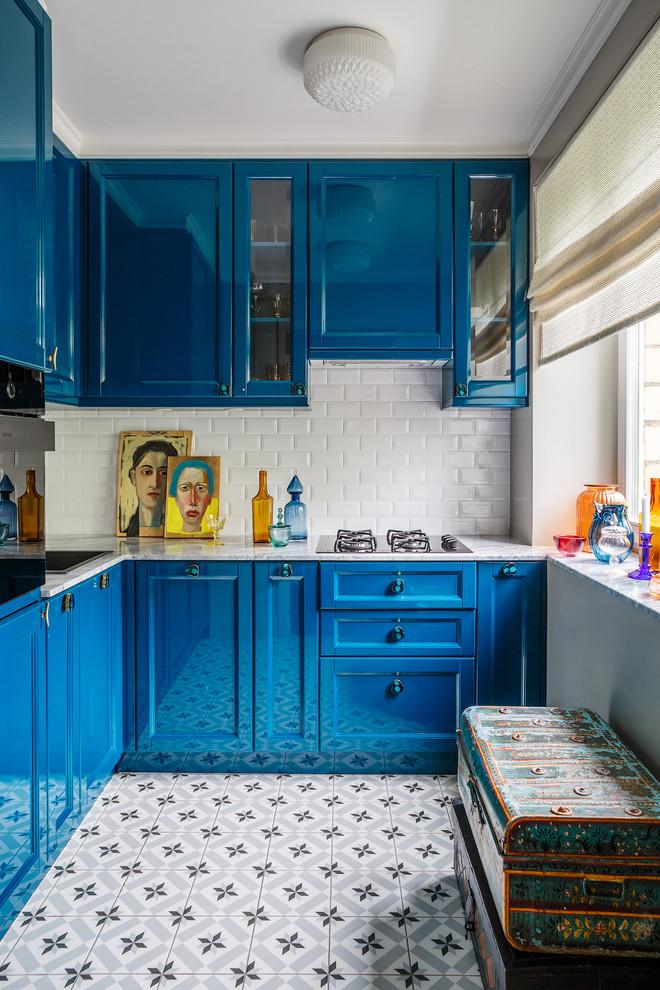 Пример оригинального дизайна интерьера: отдельная, угловая кухня в современном стиле с накладной раковиной, фасадами в стиле шейкер, синими фасадами, белым фартуком, фартуком из плитки кабанчик и черной техникой без острова