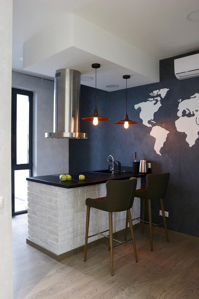 Выдающиеся фото от архитекторов и дизайнеров интерьера: маленькая параллельная кухня-гостиная в современном стиле с столешницей из гранита, черным фартуком, техникой из нержавеющей стали, паркетным полом среднего тона и полуостровом