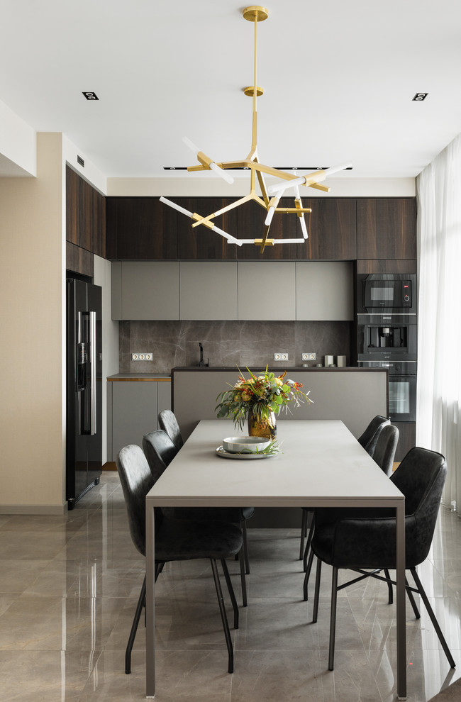 Mid-sized trendy l-shaped porcelain tile and gray floor eat-in kitchen photo in Saint Petersburg with flat-panel cabinets, gray cabinets, gray backsplash, porcelain backsplash, black appliances, gray countertops, a drop-in sink and an island