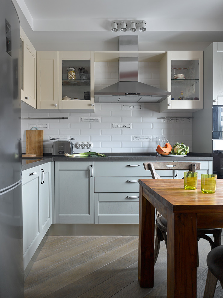 Kitchen - contemporary l-shaped brown floor kitchen idea in Moscow with shaker cabinets, gray cabinets, white backsplash, subway tile backsplash, black appliances, no island and gray countertops