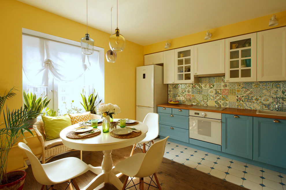 Eat-in kitchen - mid-sized traditional l-shaped eat-in kitchen idea in Moscow with recessed-panel cabinets, white cabinets, multicolored backsplash, porcelain backsplash, no island, a drop-in sink and white appliances
