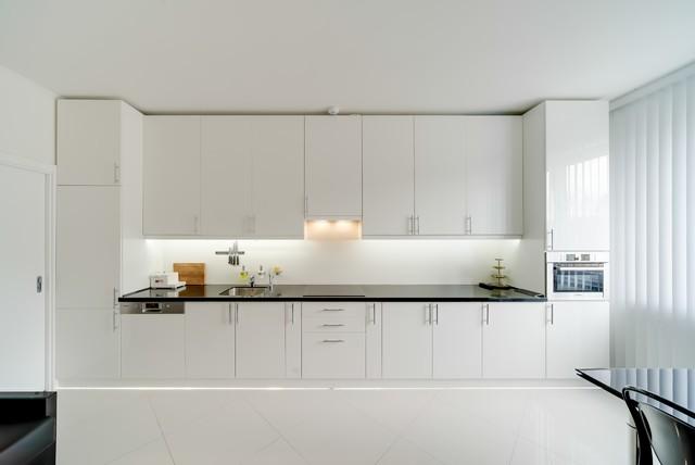 Создайте стильный интерьер: линейная кухня-гостиная в современном стиле с врезной раковиной, плоскими фасадами, белыми фасадами, белым фартуком и белым полом без острова - последний тренд