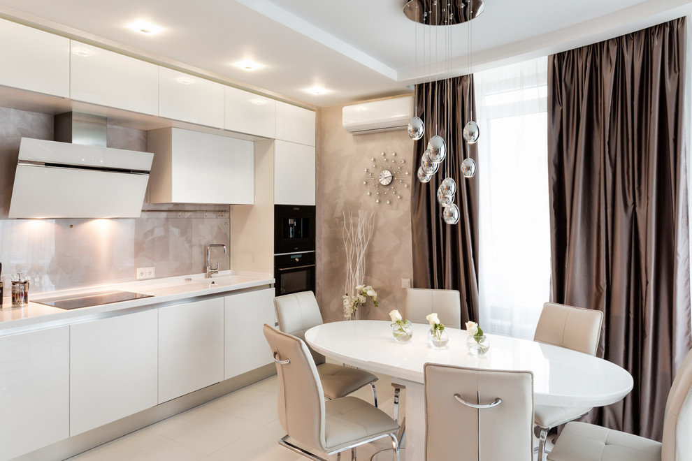 Eat-in kitchen - contemporary single-wall eat-in kitchen idea in Other with an integrated sink, flat-panel cabinets, white cabinets, beige backsplash, stone tile backsplash, black appliances and no island