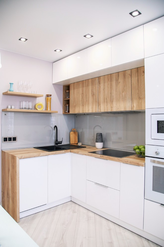 Inspiration for a small contemporary l-shaped beige floor kitchen remodel in Novosibirsk with a drop-in sink, flat-panel cabinets, white cabinets, wood countertops, gray backsplash, glass sheet backsplash and white appliances