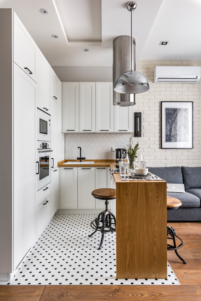Inspiration for a small contemporary u-shaped multicolored floor open concept kitchen remodel in Moscow with a drop-in sink, recessed-panel cabinets, white cabinets, wood countertops, white backsplash, white appliances, a peninsula and brown countertops