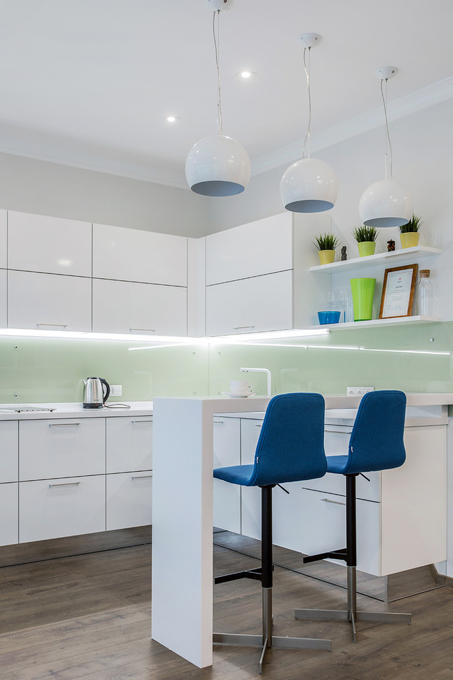 Open concept kitchen - scandinavian u-shaped dark wood floor open concept kitchen idea in Moscow with flat-panel cabinets, white cabinets, green backsplash and a peninsula
