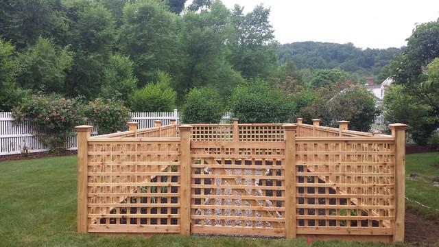 A custom lattice fence encloses a raised stone bed vegetable garden