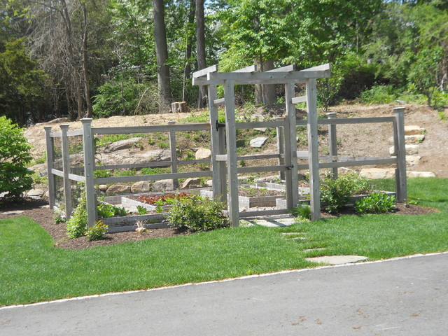 A Fenced Vegetable Garden With An Arbor Is Located In The