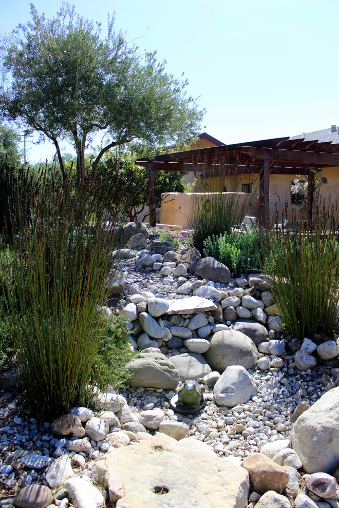 This is an example of a mediterranean backyard water fountain landscape in San Luis Obispo.