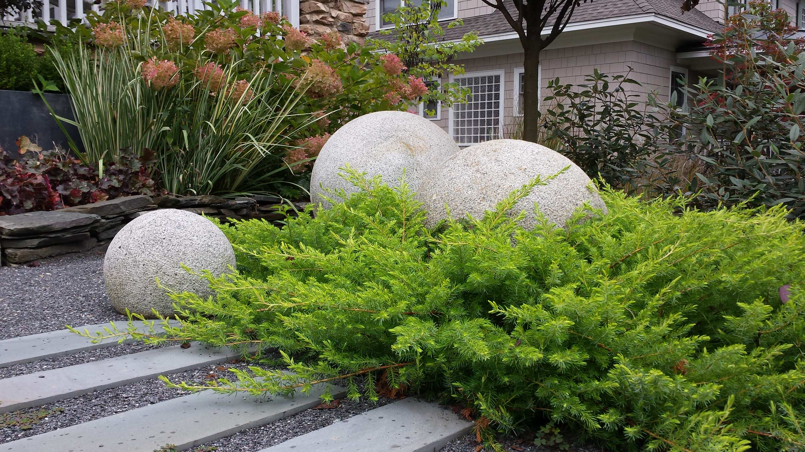 'All Gold' shore junipers with granite spheres.