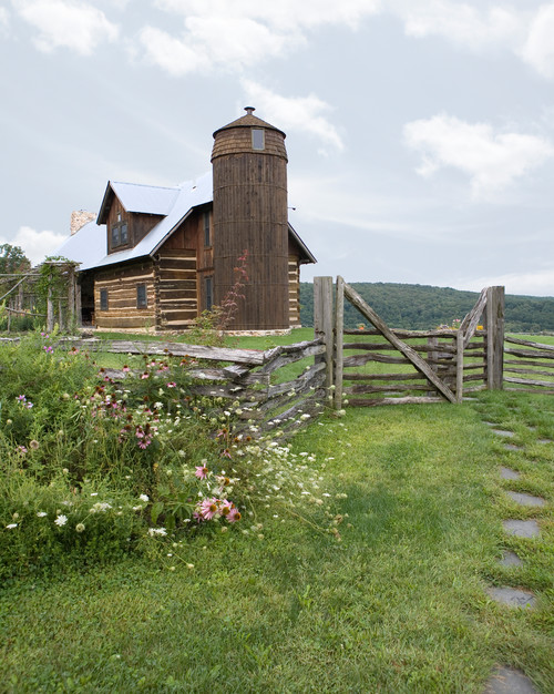 A beautiful farmhouse with a silo framed by a rustic split rail fence, a wealth of wildflowers, and a flagstone path leading up to it.
