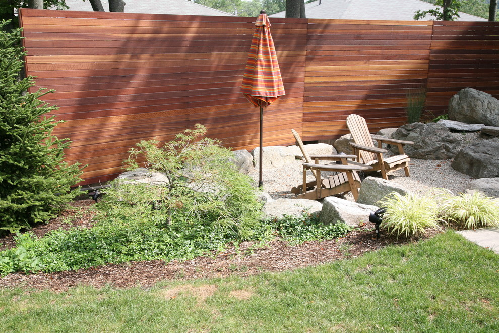 Photo of a mid-sized contemporary partial sun backyard gravel formal garden in Boston for winter.