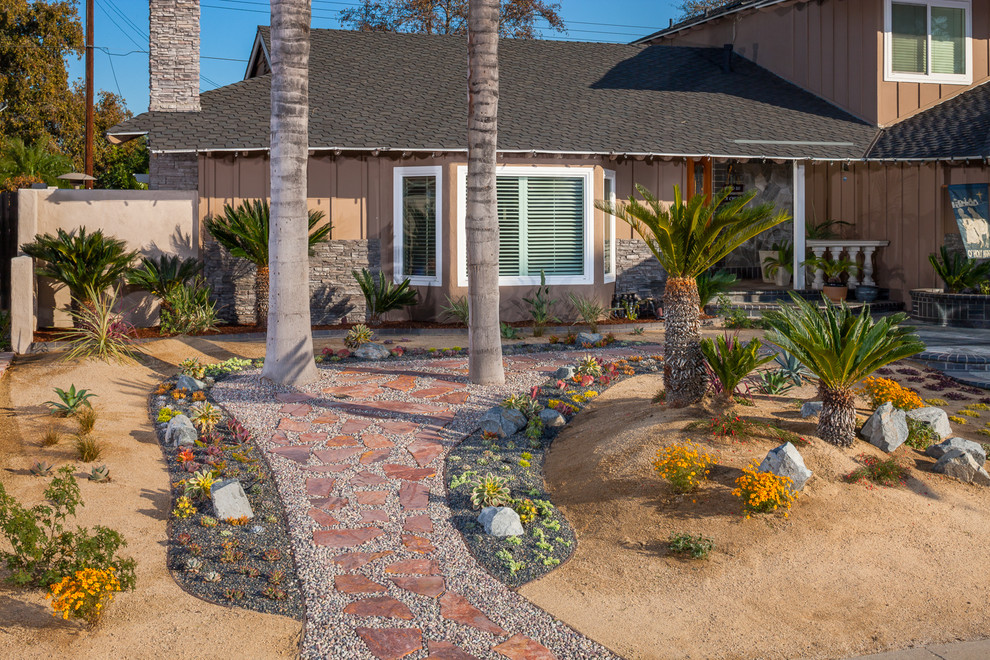 This is an example of a mid-sized tropical drought-tolerant, full sun and desert front yard gravel landscaping in Orange County.