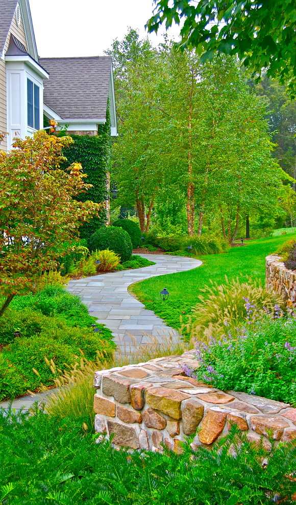 Photo of a large traditional side yard stone landscaping in New York.