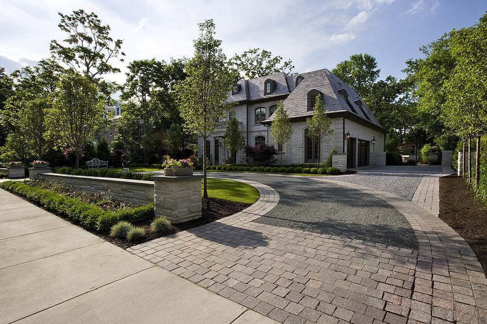 Design ideas for a large traditional full sun front yard stone driveway in Chicago for summer.