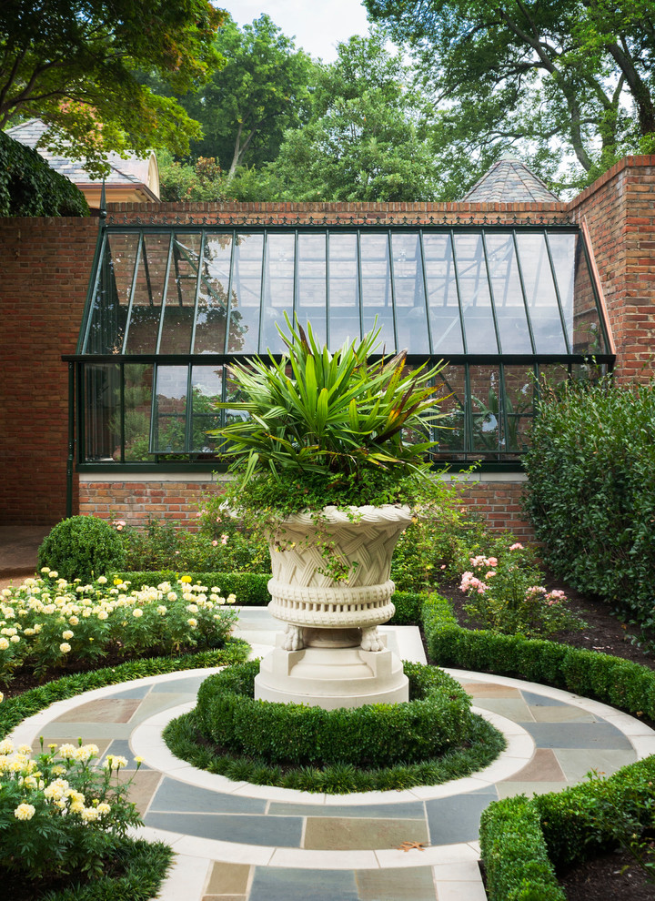 Inspiration for a mid-sized traditional partial sun courtyard stone landscaping in Other.