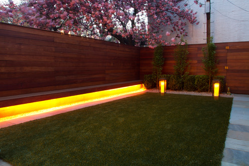 Here is a backyard with an interesting lighting setup. There is a long light placed underneath a bench making the underside of the bench glow. This is great for an ambient light and a warm welcoming appeal.