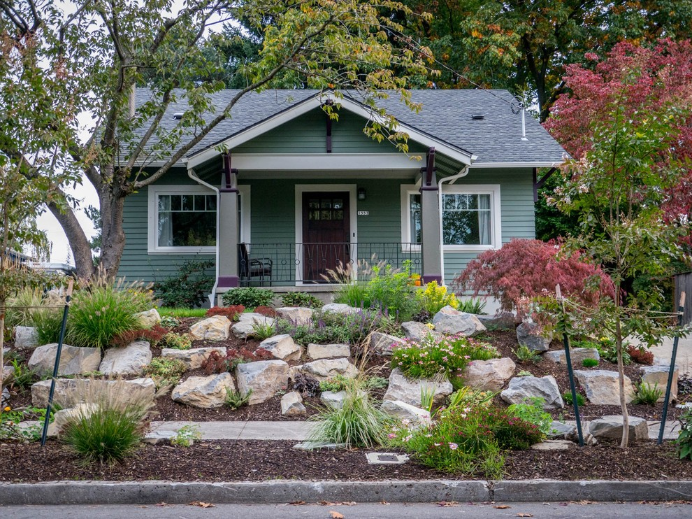 Photo of a mid-sized craftsman full sun and rock front yard landscaping in Portland.