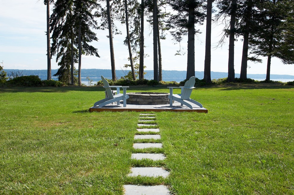 This is an example of an eclectic full sun backyard stone landscaping in Seattle with a fire pit.