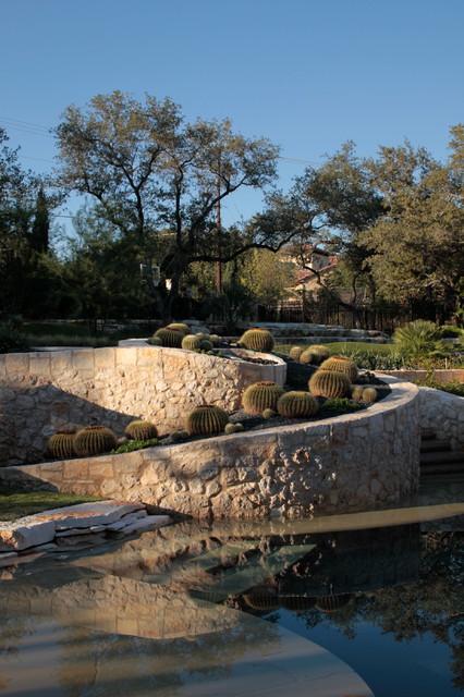 Ejemplo de jardín mediterráneo, en patio trasero, con muro de contención