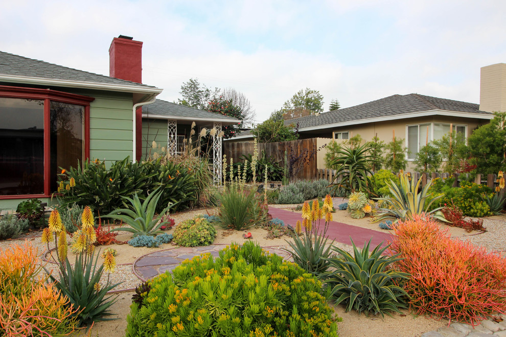 This is an example of a small eclectic drought-tolerant and partial sun front yard gravel garden path in Los Angeles for summer.