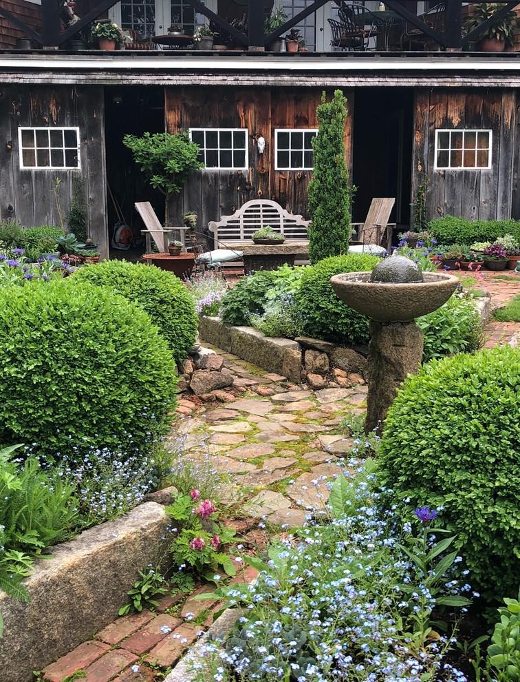 Design ideas for a farmhouse full sun backyard brick garden path in Boston.
