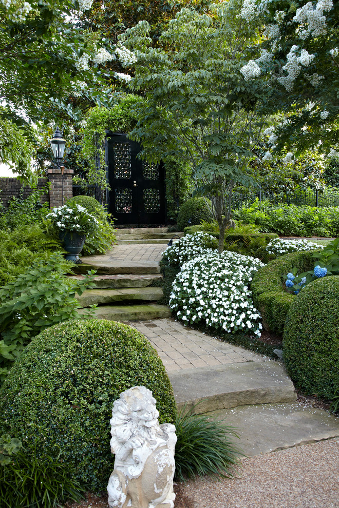 Inspiration for a traditional backyard brick landscaping in Other for summer.
