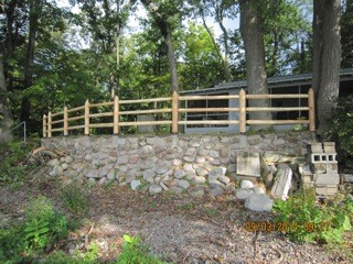 Cedar Post and Rail Fence Installed on a Retaining Wall