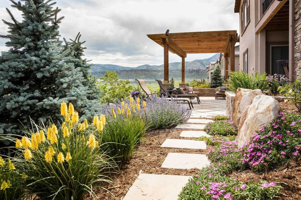 Design ideas for a mid-sized traditional full sun and drought-tolerant backyard stone landscaping in Denver for summer.