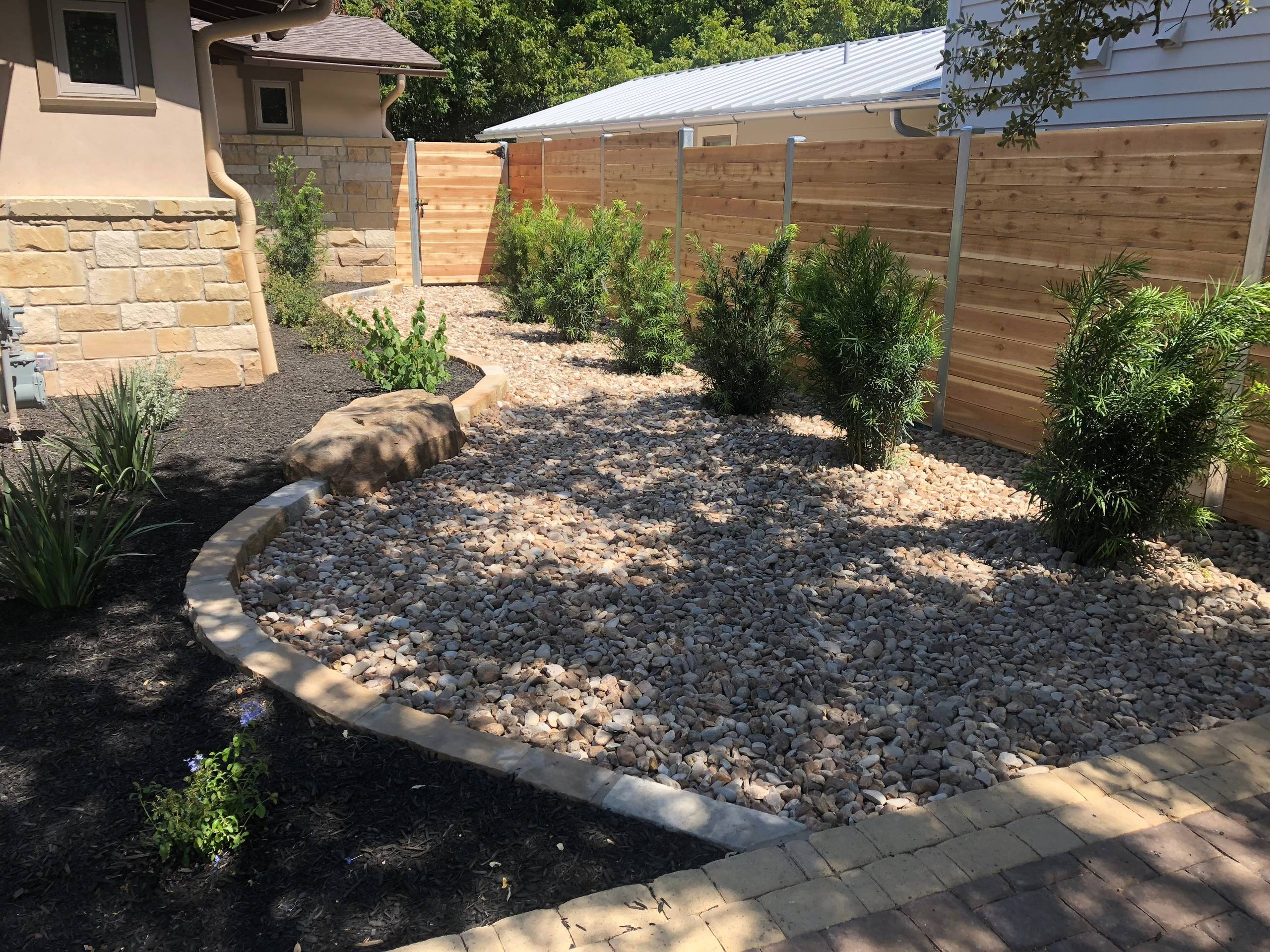"""Combination of mulch and Colorado River Rock with """"future"""" privacy shrubs"""