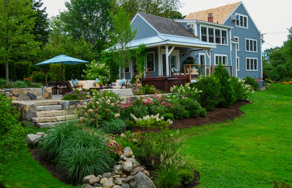 This is an example of a mid-sized farmhouse full sun backyard stone landscaping in Boston.