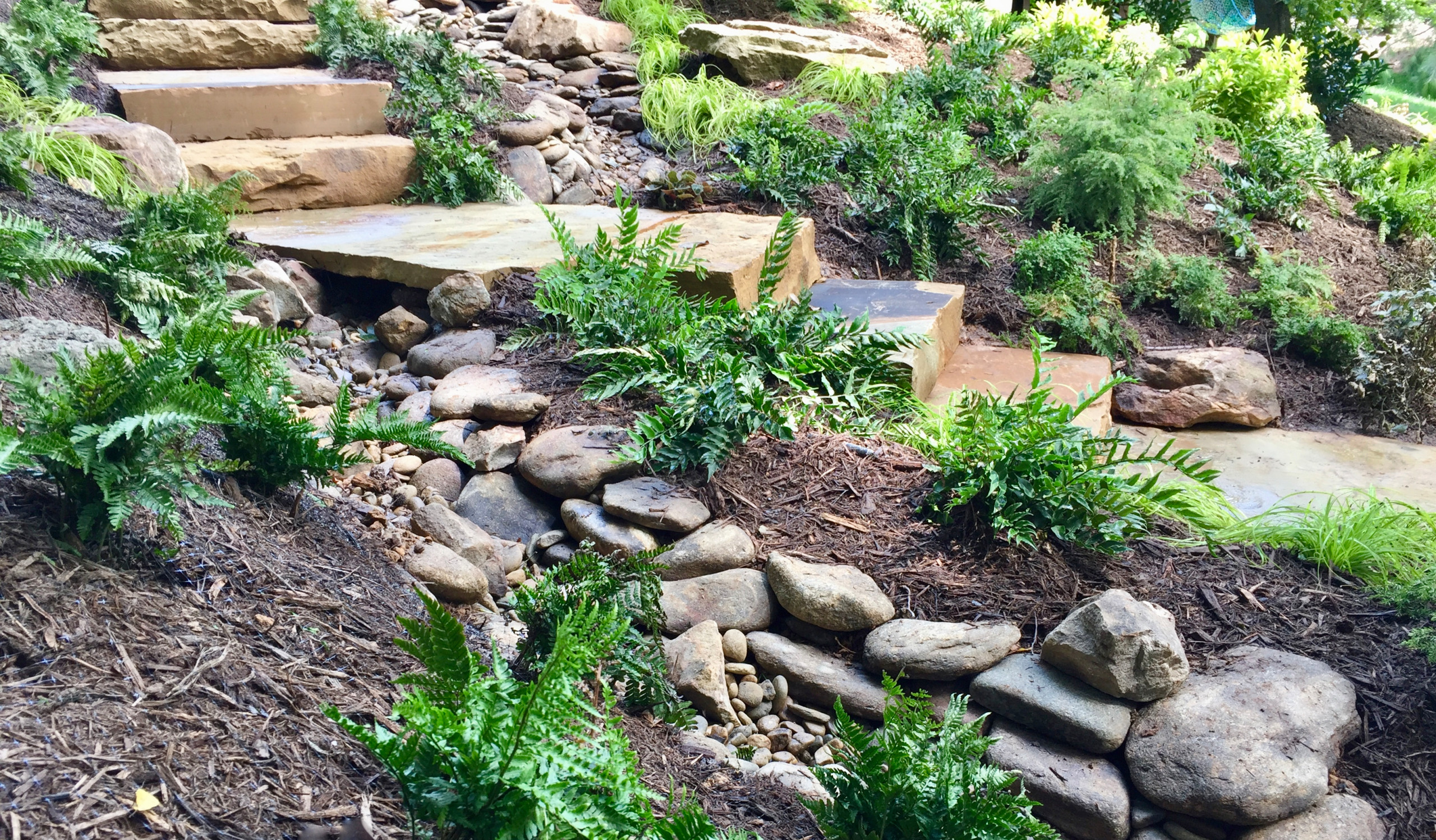 Creek bed under stone slab bridge