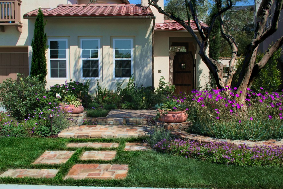 This is an example of a mid-sized mediterranean partial sun front yard stone landscaping in Los Angeles.
