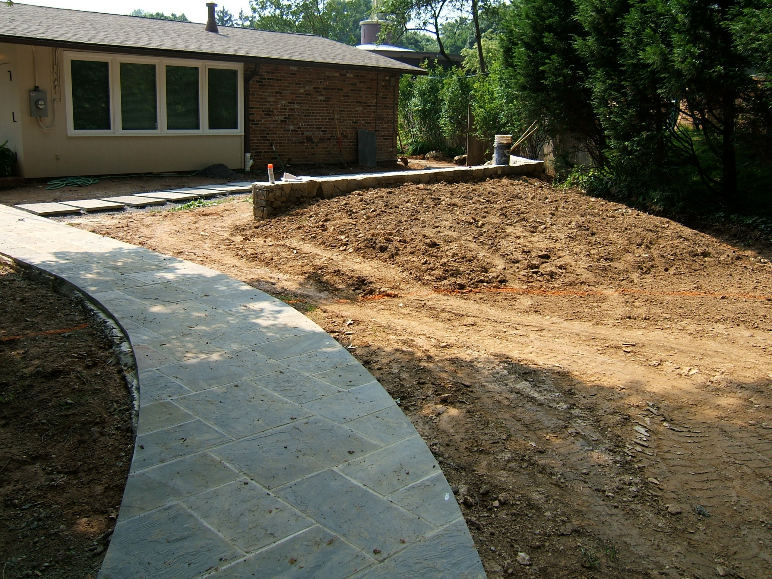 Curved lead walk, path to walled patio with privacy bern
