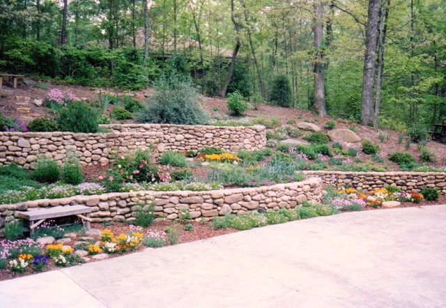 Curved stone retaining walls and huge boulders on hill Rustic