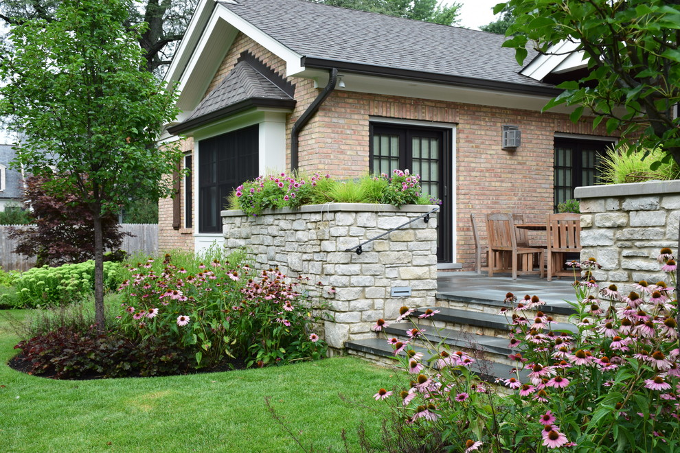 Photo of a mid-sized traditional full sun backyard stone landscaping in Chicago for summer.