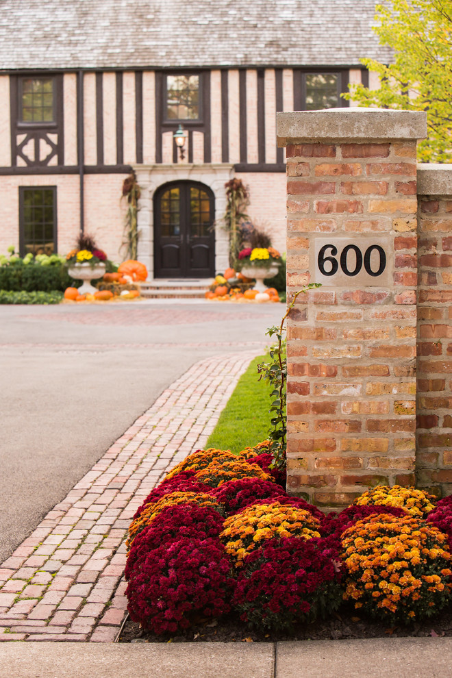 Inspiration for a large traditional full sun front yard brick driveway in Chicago for fall.